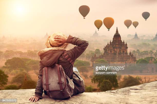 myanmar, young hipster woman traveller backpacker sitting watch beautiful landscape bagan mandalay ancient pagoda in bagan, mandalay myanmar. - rucksacktourist stock-fotos und bilder