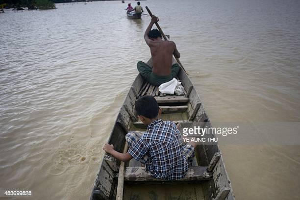 MyanmarAsiafloodsweatherSCENE by Ye Aung THU This photo taken on August 11 2015 shows 39yearold vegetable farmer Aung Myo Tun and his son riding in...