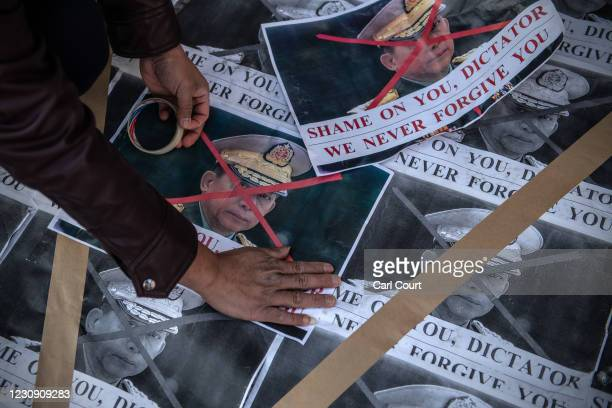 Myanmarese man tapes over the face of Myanmar military chief Min Aung Hlaing on posters placed on the ground during a demonstration against the...