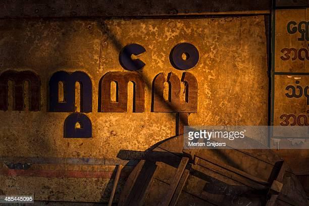 myanmarian letters on store in sunlight - merten snijders stock-fotos und bilder
