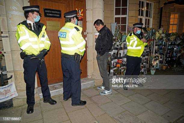 Myanmar's Ambassador to the United Kingdom, Kyaw Zwar Minn, waits unsuccessfully for an answer on the intercom, as police officers stand on duty...