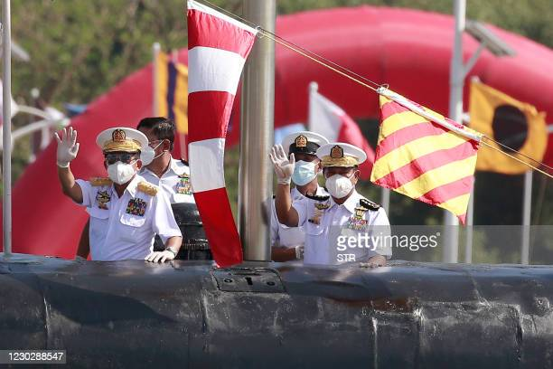 Myanmar's commander-in-chief Senior General Min Aung Hlaing waves as he inspects a submarine during the welcoming ceremony for new warships and a...