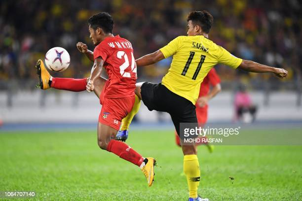 Myanmar's defender Win Moe Kyaw and Malaysia's midfielder Safawi Rasid fight for the ball during the AFF Suzuki Cup 2018 football match between...