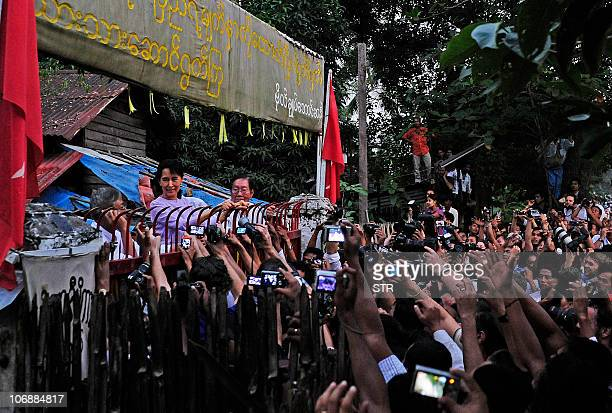 OUT Myanmar's detained opposition leader Aung San Suu Kyi appears at the gate of her house in front of cheering supporters after her release in...