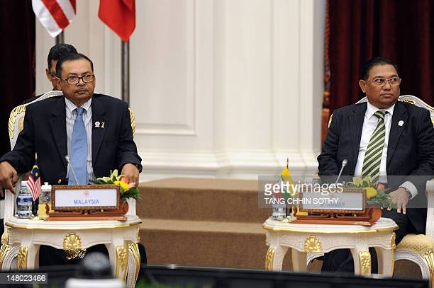 Myanmar's Foreign Minister Nyan Win and an unidentified representative of Malaysia's foreign ministry sit during the Association of Southeast Asian...