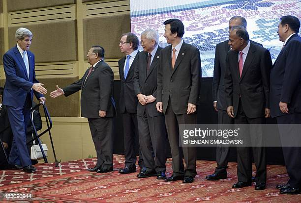 Myanmars Foreign Minister Wunna Maung Lwin greets US Secretary of State John Kerry to a group photo during the East Asia Summit Foreign Ministers...