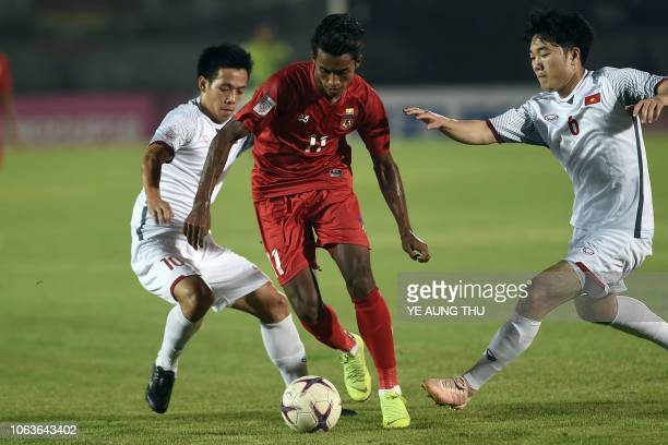 Myanmar's forward Maung Maung Lwin fights for the ball with Vietnam's forward Nguyen Van Quyet and midfielder Luong Xuan Truong during the AFF Suzuki...