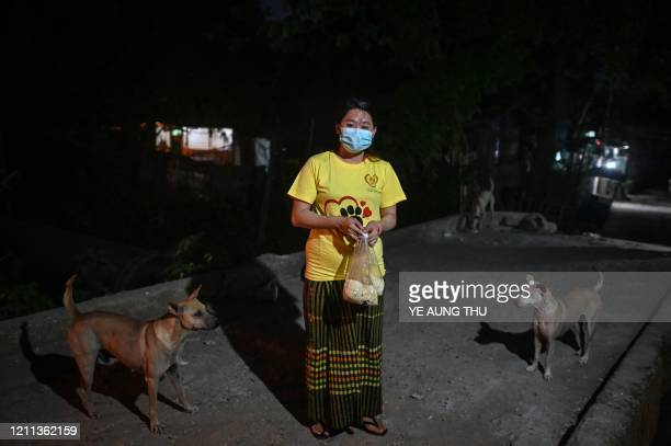 Myanmar's Hnin Si Myint dog shelter founder poses for a picture as she conducts her daily feeding of stray dogs on the streets of Yangon Myanmar on...