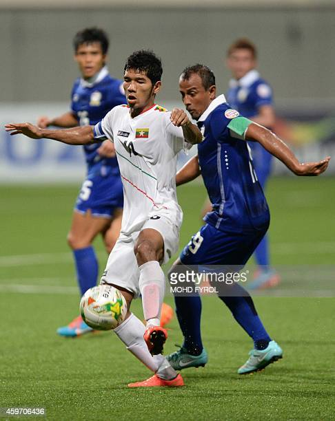 Myanmar's Kyaw Ko Ko controls the ball against Thailand player Adul Lahsom during the AFF Suzuki 2014 Cup football match between Thailand and Myanmar...