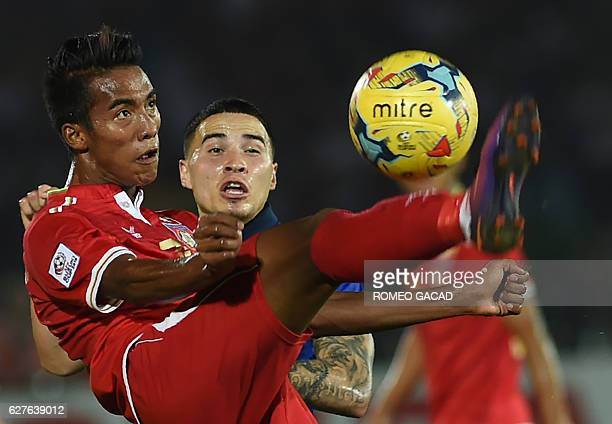 Myanmar's Maung Maung Lwin and Thailand's Tristan Do vie for the ball during the AFF Suzuki Cup semifinal football match at the Thuwanna Football...