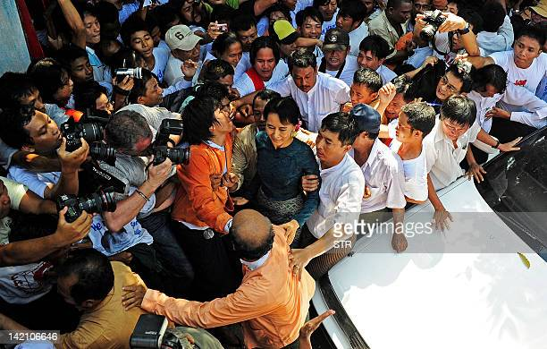 Myanmar's newlyreleased opposition leader Aung San Suu Kyi is surrounded by supporters and photographers as she arrives at her National League for...
