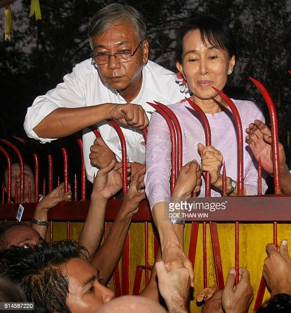 Myanmar's opposition leader Aung San Suu Kyi appears with Htin Kyaw a senior National League for Democracy official at the gate of her house in front...
