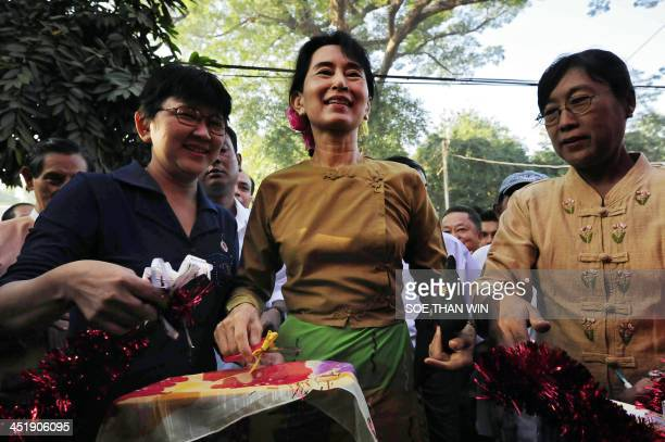 Myanmar's opposition leader Aung San Suu Kyi smiles after cutting a ribbon to open a function at her National League for Democracy headquarters ahead...