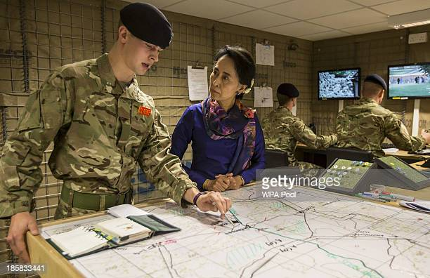 Myanmar's opposition leader Aung San Suu Kyi wearing a remembrance poppy listens to Officer Cadet Ed Clarke in a simulation of a Forward Operating...