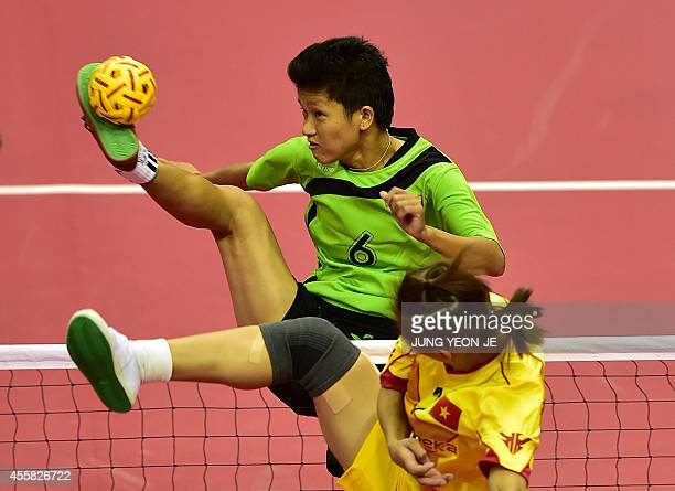 Myanmar's Phyu Than Phyu strike the ball against Vietnam's Thi Xuyen Duong in the women's double preliminary group B sepaktakraw match during the...