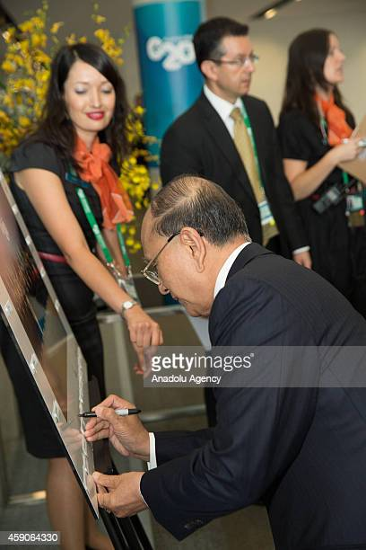 Myanmar's President U Thein Sein signs the official G20 Leaders' Summit group photograph in Brisbane, Australia, on November 16, 2014.