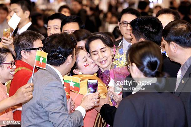 Myanmar's State Counsellor and Foreign Minister Aung San Suu Kyi is welcomed by Myanmar people living in Japan on arrival at Haneda International...