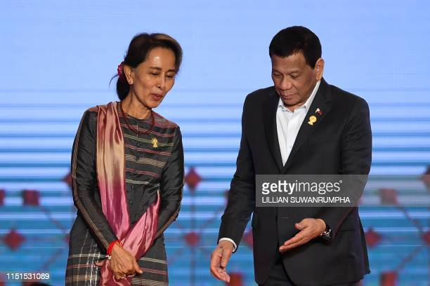 Myanmar's State Counsellor Aung San Suu Kyi and Philippines' President Rodrigo Duterte walk off the stage after posing for photos during the opening...