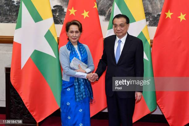 Myanmar's State Counsellor Aung San Suu Kyi, left, shakes hands with Chinese Premier Li Keqiang as they pose for media before their meeting on April...