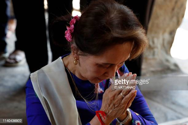 Myanmar's State Counsellor Aung San Suu Kyi prays during her visit to the Angkor Wat temple in Siem Reap province on May 1, 2019. - Aung San Suu Kyi...