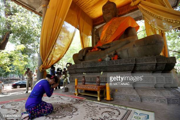 TOPSHOT Myanmar's State Counsellor Aung San Suu Kyi prays in front of a Buddha statue during her visit to the Bayon temple in Siem Reap province on...