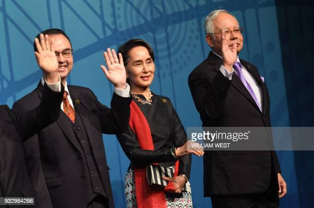 Myanmar's State Counsellor Aung San Suu Kyi waves to the cameras with Philippines' Foreign Secretary Alan Peter Cayetano and Malaysia's Prime...