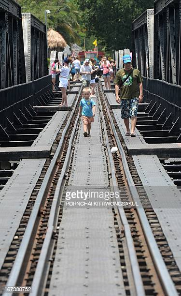 WITH 'MyanmarThailandJapanWWIIhistoryrailtourism' FEATURE by Kelly Macnamara In a picture taken on April 24 foreign tourists walk on a railway bridge...