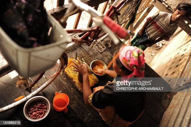 Myanmar-unrest-religion-migration,FOCUS by Amelie Bottollier-Depois This picture taken on October 11, 2012 shows a Muslim Rohingya preparing chilli...