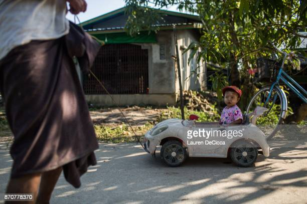 Myat Phone Pyae is pulled by his grandfather in a toy car in the Sin Ma Kaw Village on November 5 2017 in Yangon Myanmar The Sin Ma Kaw village is...
