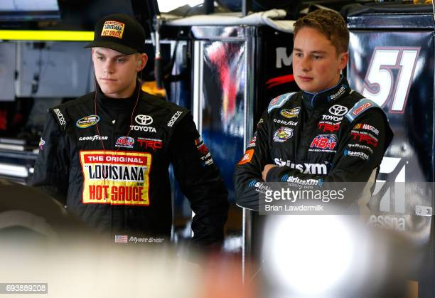 Myatt Snider driver of the Louisiana Hot Sauce Toyota speaks with Christopher Bell driver of the JBL Toyota in the garage area during practice for...