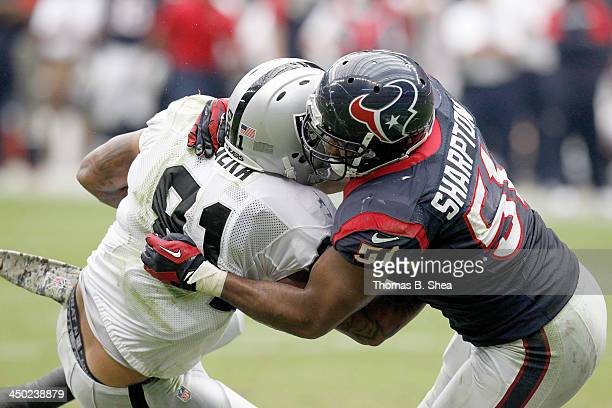 Mychal Rivera of the Oakland Raiders is tackled by Darryl Sharpton of the Houston Texans on November 17 2013 at Reliant Stadium in Houston Texas
