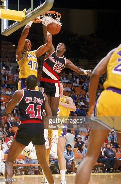 Mychal Thompson of the Los Angeles Lakers dunks over Jerome Kersey of the Portland Trail Blazers during an NBA game at the Great Western Forum in Los...