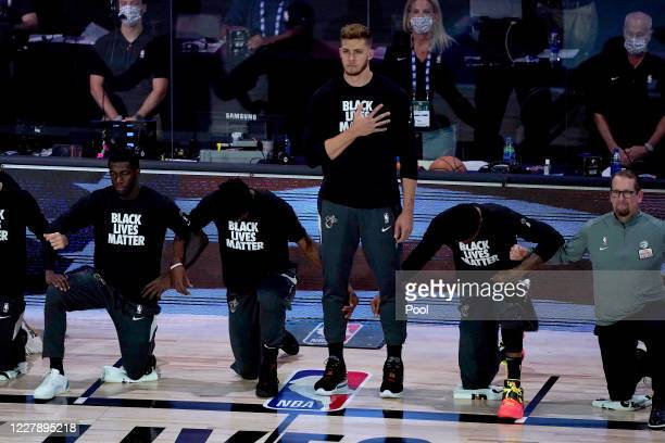 Myers Leonard of the Miami Heat stands during the National Anthem as his teammates take a knee prior to the game against the Toronto Raptors at HP...