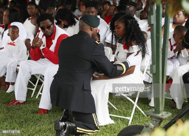 Myeshia Johnson is presented with a folded American flag by a military honor guard member during the burial service for her husband US Army Sgt La...