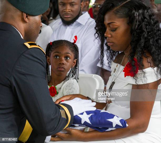 Myeshia Johnson is presented with the US flag that was draped over the casket of her husband Sgt La David Johnson during his burial service at Fred...