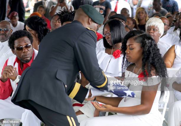 Myeshia Johnson the wife of Army Sgt La David Johnson is presented a flag during his the burial at Fred Hunter's Hollywood Memorial Gardens in...