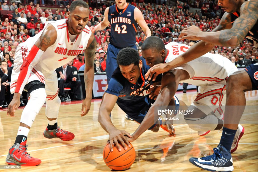 Myke Henry #20 of the Illinois Fighting Illini and Shannon Scott #3 of the Ohio State Buckeyes dive for a loose ball in the first half as Deshaun Thomas #1 of the Ohio State Buckeyes watches on March 10, 2013 at Value City Arena in Columbus, Ohio.