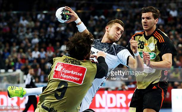 Mykola Bilyk of Kiel challenges for the ball with Mait Patrail and Erik Schmidt of HannoverBurgdorf during the DKB HBL Bundesliga match between THW...