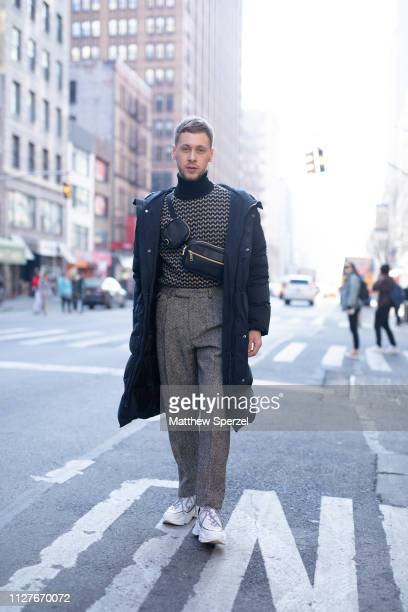 Mykola Hruts is seen on the street during Men's New York Fashion Week wearing navy coat black leather crossbody bag grey wool trousers grey with...