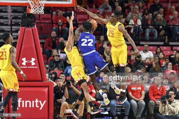 Myles Cale of the Seton Hall Pirates drives to the basket between Anthony Cowan Jr #1 and Jalen Smith of the Maryland Terrapins a college basketball...