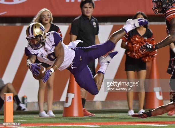 Myles Gaskin of the Washington Huskies leaps into the end zone for a touchdown in the first half of a game against the Utah Utes at RiceEccles...