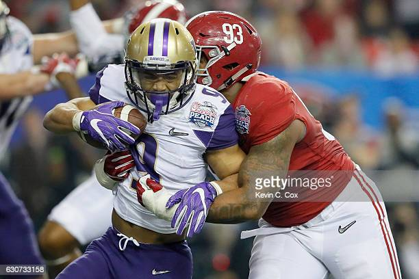 Myles Gaskin of the Washington Huskies runs the ball against Jonathan Allen of the Alabama Crimson Tide during the 2016 ChickfilA Peach Bowl at the...