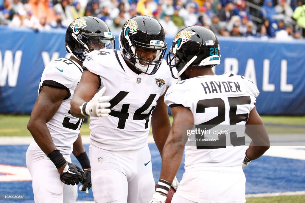Myles Jack #44 of the Jacksonville Jaguars celebrates with Telvin Smith #50 and D.J. Hayden #25 after interception a pass by Eli Manning #10 of the New York Giants in the fourth quarter and scoring a touchdown at MetLife Stadium on September 9, 2018 in East Rutherford, New Jersey.