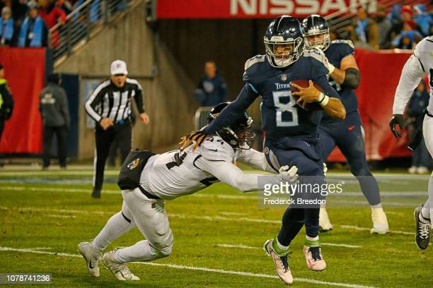 Myles Jack of the Jacksonville Jaguars dives to tackle quarterback Marcus Mariota of the Tennessee Titans at Nissan Stadium on December 6 2018 in...