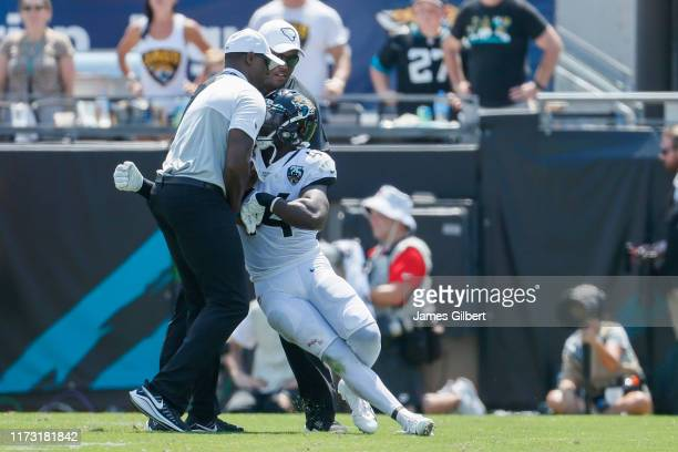 Myles Jack of the Jacksonville Jaguars is led off the field after being ejected in the first half against the Kansas City Chiefs at TIAA Bank Field...