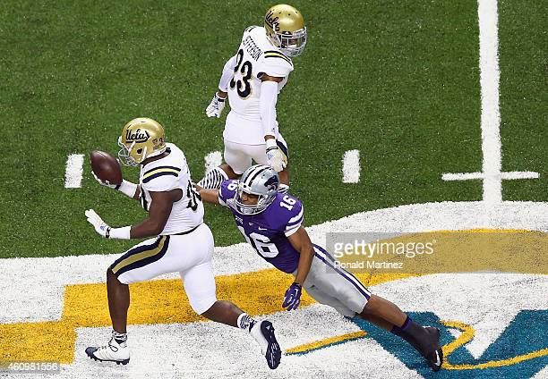 Myles Jack of the UCLA Bruins runs a pass interception against Tyler Lockett of the Kansas State Wildcats in the second quarter during the Valero...
