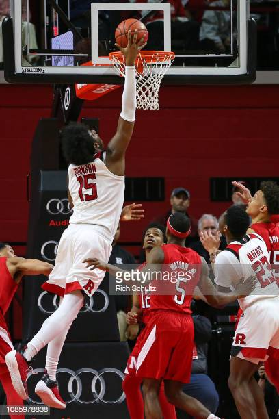 Myles Johnson of the Rutgers Scarlet Knights makes a shot over Thomas Allen and Glynn Watson Jr #5 of the Nebraska Cornhuskers during the second half...