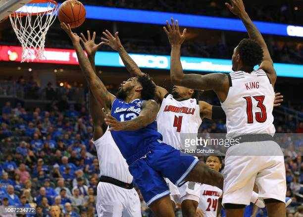 Myles Powell of the Seton Hall Pirates attempts a shot as Akoy Agau Khwan Fore and VJ King of the Louisville Cardinals defend during the second half...