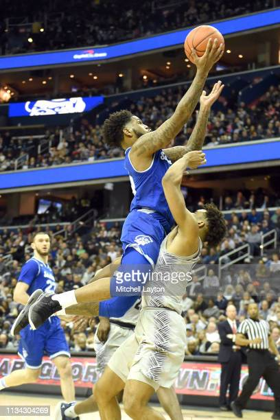 Myles Powell of the Seton Hall Pirates drives to the basket over James Akinjo of the Georgetown Hoyas during a college basketball game at the Capital...
