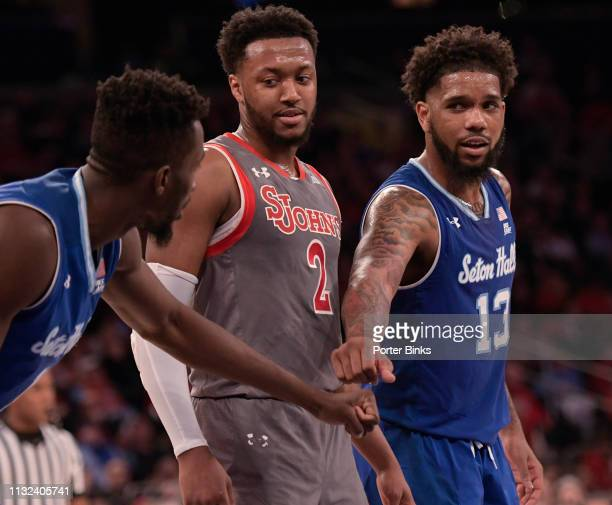 Myles Powell of the Seton Hall Pirates right encourages teammate Michael Nzei as Shamorie Ponds of the St John's Red Storm looks on at Madison Square...